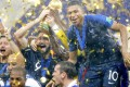 Olivier Giroud, alongside Kylian Mbappe, raises the trophy after France beat Croatia 4-2 to win the country's second World Cup at Luzhniki Stadium in Moscow. Photo: Kyodo