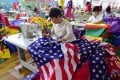 """This July 13, 2018 photo shows Chinese employees sewing US flags in Fuyang in Anhui province. As the Sino-US trade war rages, a factory set amid corn and mulberry fields in central China stitches together US and """"Trump 2020"""" flags -- and business is good. Photo: AFP"""