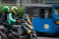 A Grab motorcycle-taxi transporting a passenger to her destination in Jakarta, while a three-wheeled bajaj taxi (R) sits parked on the roadside. Photo: AFP