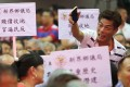Members held placards and shouted slogans during Monday's meeting. Photo: Winson Wong