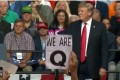 """A rally participant holds up a """"We are Q"""" poster at Donald Trump's recent rally in Tampa, Florida. Photo: Fox News"""