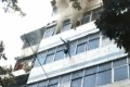 The child is thrown from the burning building, landing safely below. Photo: Handout