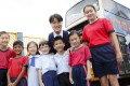 Principal Wong Wai-lap (back centre) with primary schoolchildren in front of their KMB bus library at Tung Tak School in Hong Kong's New Territories. Photo: Raymond Mak