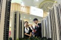 A sales assistant (on right) speaks to a customer at a real estate exhibition in Shanghai on April 30, 2015. Photo: Reuters