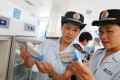 Officials from China's food and drug administration carry out checks at a vaccines production facility. Photo: AFP