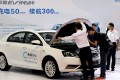 Men look at an electric car from Caocao Zhuanche, a chauffeur ride-hailing platform backed by Zhejiang Geely Holding Group, at a new energy vehicle trade fair in Zhengzhou, Henan province. Photo: Reuters