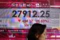 A woman walks past a bank electronic board showing the Hong Kong share index outside a Hong Kong local bank on Aug. 13, 2018. Photo: AP