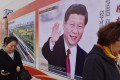 """People walk past a poster featuring Chinese President Xi Jinping with a slogan reading """"Chinese Dream, People's Dream"""" in Beijing. Xi's medium-to-long-term plans, in particular its plan to move up the value chain and compete directly with the US in manufacturing through the Made in China 2025 campaign, are the true targets of the US trade war, rather than trade imbalances. Photo: AFP"""