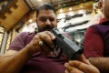 A man checks a gun at a weapons shop in Baghdad, Iraq on August 11, 2018. Photo: Reuters