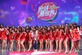 A male staffer poses with showgirls at the booth of live-streaming app Xigua on the last day of ChinaJoy. Photo: SCMP/ Zheping Huang