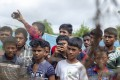 """Rohingya refugees gather near the fence in the """"no-man's-land"""" zone between Myanmar and Bangladesh border. Photo: AFP"""