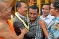 Former Cambodian opposition lawmaker Um Sam An (2nd L) hugs a land rights activist after he was released by royal pardon. Photo: AFP