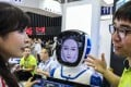 A visitor interacts with a robot, designed by Xi'an Sammer Technology, at the 2018 Smart China Expo held in Chongqing.