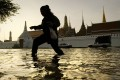 A woman walks through floodwaters in front of the Grand Palace, Bangkok in 2011. File photo: AFP