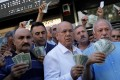 Businessmen holding US dollars stand in front of a currency exchange office in Ankara on August 14 in response to Turkish President Recep Tayyip Erdogan's call to Turks to sell their dollar and euro savings to support the lira. Photo: Reuters