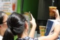 Bubble tea fans take selfies at Tiger Sugar in Causeway Bay. Photo: SCMP/ Dickson Lee
