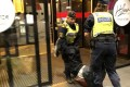 Swedish police officers carry one of the Chinese tourists out of the Stockholm hostel. Photo: Handout