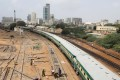 A passenger train passes labourers working on a railway track near City Station in Karachi. Photo: Reuters