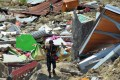 A man carries items retrieved from the rubble. Photo: AP