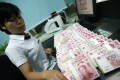 A Chinese bank clerk counts stacks of 100-yuan notes at a bank in Huaibei. Photo: AFP