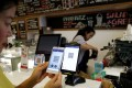 A Singaporean woman pays for her coffee at a cashless cafe. Photo: Reuters