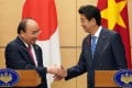 Vietnam Prime Minister Nguyen Xuan Phuc (left) and Japan Prime Minister Shinzo Abe shake hands after their joint press conference in Tokyo on Monday. Photo: AFP