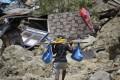 A man carries belongings from his toppled house in the Balarola neighbourhood of Palu city. Photo: AP
