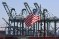 The US flag flies over Chinese shipping containers being unloaded at the Port of Long Beach, Los Angeles. Photo: AFP