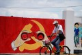 A man rides his bicycle next to a mural showing an emblem of the Communist Party of China along a street in Shanghai, China, 2018. Photo: Reuters