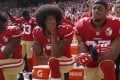 Former San Francisco 49ers quarterback Colin Kaepernick (centre) flanked by Eli Harold (left) and Eric Reid during the national anthem in October 2016. Photo: TNS