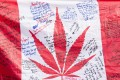 People hold up a Canadian flag with a marijuana logo on it outside a government cannabis store in Montreal. Photo: AP