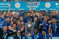 Leicester City players and chairman Vichai Srivaddhanaprabha (C) a pose with the Premier league trophy after winning the league. Photo: AFP