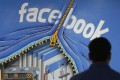 A Facebook employee walks past a sign at the company's headquarters in Menlo Park, California, in March 2013. Facebook is an example of a company with a business model built around intangible capital. Photo: AP