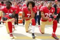 San Francisco 49ers quarterback Colin Kaepernick (centre), takes a knee with teammates Eli Harold (left), and Eric Reid (right) during the US national anthem before the NFL game against the Dallas Cowboys in October, 2016. Photo: EPA-EFE