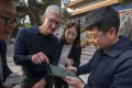Liu Zhipeng (1st R), one of the founders of Xichuangzhu APP, shows Apple's CEO Tim Cook how to write calligraphy on an iPad with the Apple Pencil at the Beijing Confucian Temple, Oct. 10, 2018. Photo: Xinhua