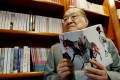 Novelist Louis Cha holding a copy of 'Book and Sword, Gratitude and Revenge' at his office in 2002. Photo: Reuters