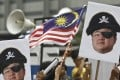 Portraits of Jho Low held aloft during a protest in Kuala Lumpur, Malaysia. Photo: AP