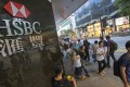 """People walk past the HSBC logo in Central District on October 29. HSBC posted strong third-quarter profits, despite a leaked memo, revealed in September, from investment bankers that criticised the company's """"utterly failed"""" investment banking strategy. Photo: EPA-EFE"""