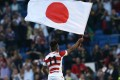 Japan's wing Kotaro Matsushima waves the Japanese national flag as the team celebrate their victory over South Africa in the 2015 Rugby World Cup. Photo: AFP