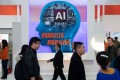 Visitors walk past a stand with artificial intelligence security cameras using facial recognition technology at the 14th China International Exhibition on Public Safety and Security in Beijing on October 24. Photo: AFP
