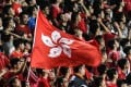 Local football fans hold up the Hong Kong flag during a match against Malaysia in Hong Kong. A new law that punishes disrespect for China's national anthem with up to three years' imprisonment may also apply to Hong Kong and Macau, state media reported. Photo: Anthony Wallace