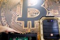 FILE PHOTO: A cryptocurrency mining computer is seen in front of bitcoin logo during the annual Computex computer exhibition in Taipei, Taiwan, June 5, 2018. REUTERS/Tyrone Siu/File Photo