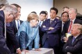 Photo released on Twitter by the German Government's spokesman Steffen Seibert on June 9, 2018 and taken by the German government's photographer Jesco Denzel shows US President Donald Trump (R) talking with German Chancellor Angela Merkel (C) and surrounded by other G7 leaders during a meeting of the G7 Summit in La Malbaie, Quebec, Canada. The photo went viral, popping up all over social media, sometimes in its original form sometimes altered for humorous or satirical ends. Photo: AP