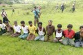 Ten Rohingya Muslim men and boys kneeling in a field in a Rakhine village last year. They were later found dead in a mass grave. Reuters reporters Wa Lone and Kyaw Soe Oo have been sentenced to seven years in jail, after investigating the killing. Photo: Reuters