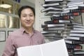Scientist He Jiankui poses with 'The Human Genome', a book he edited. Photo: Handout