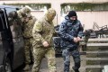 A Ukrainian sailor, right, is escorted by a Russian intelligence agency FSB officer to a courtroom in Simferopol, Crimea, on Tuesday. Photo: AP