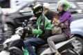 A woman rides on the back of a motorbike, part of technology start-up Go-Jek's ride-hailing service, on a busy street in central Jakarta, Indonesia. Photo: Reuters