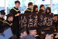 Students protest against the jailing of democracy activists, at the graduation ceremony of the Chinese University of Hong Kong on November 15. Photo: Felix Wong