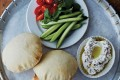 Crudités, pita bread and hummus, in an image from the book.