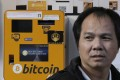 A man walks past the Bitcoin ATMs in Hong Kong, Thursday, Dec. 21, 2017. Bitcoin is the world's most popular virtual currency. Such currencies are not tied to a bank or government and allow users to spend money anonymously. They are basically lines of computer code that are digitally signed each time they are traded. (AP Photo/Kin Cheung)